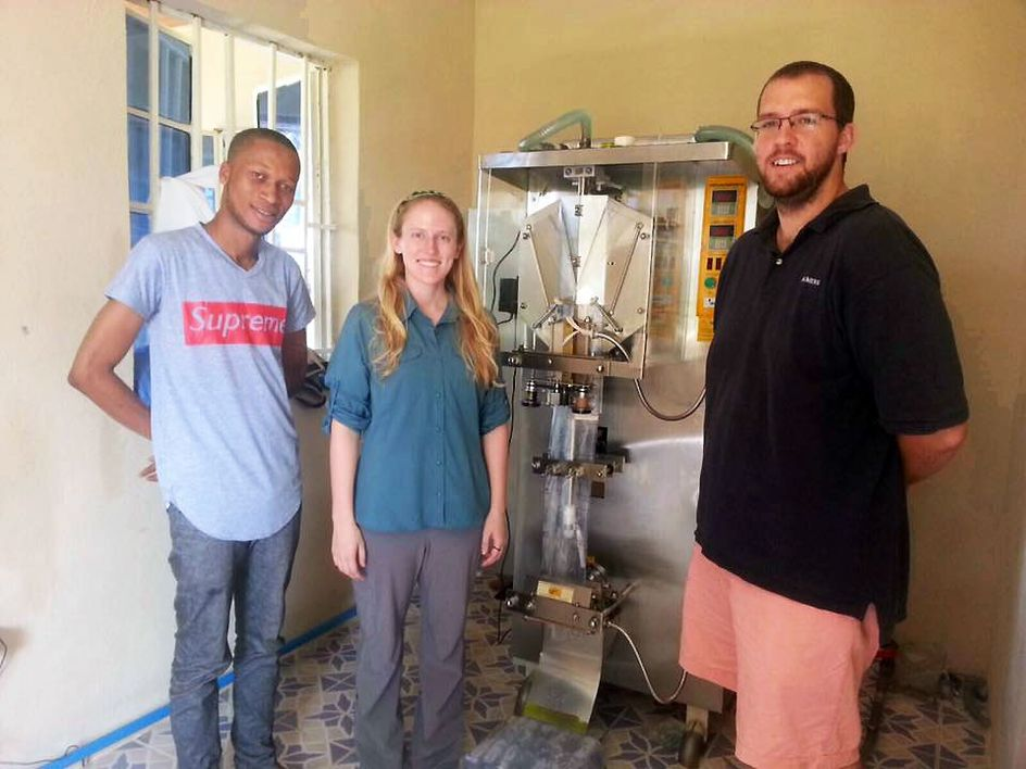 Kolar and Asher are seen with the water packing device used at the Sola Wata Water Packaging Center in Sierra Leone.
