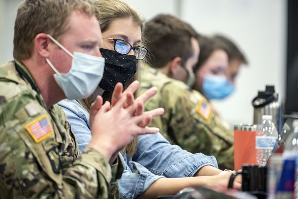 Students working with members of the National Guard.