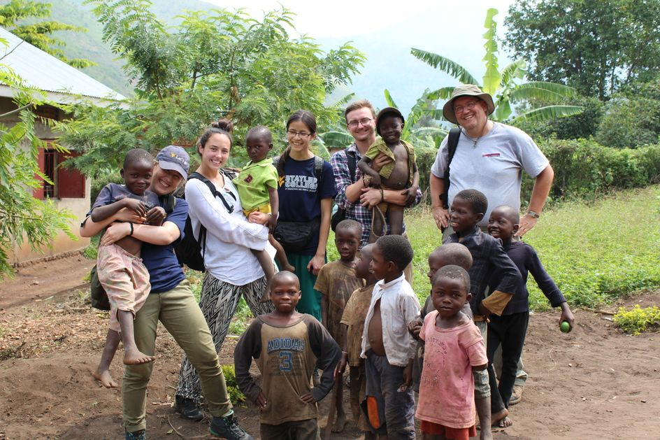 Members from WVU Engineers Without Borders hold a WVU flag in the mountains of Uganda